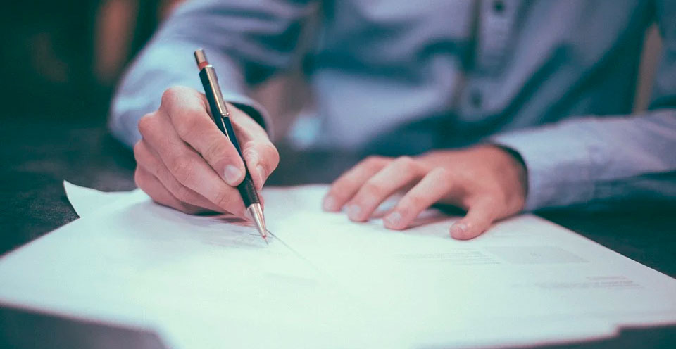 imagem de mãos escrevendo sob a mesa representando uma tradução certificada