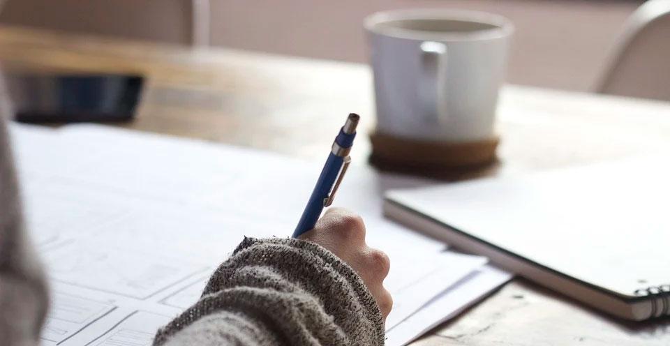 imagem de uma mão escrevendo no papel uma tradução certificada