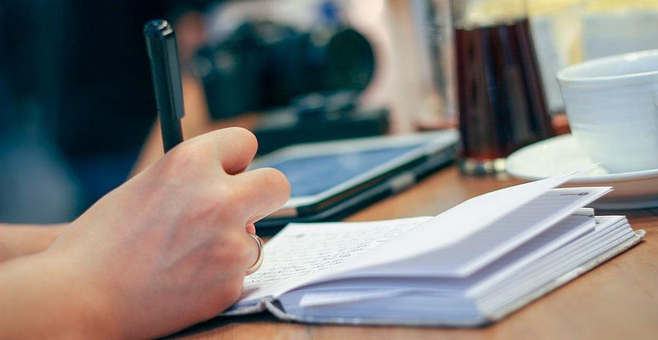 imagem de mãos escrevendo anotações em um caderno como se estivesse fazendo uma tradução certificada