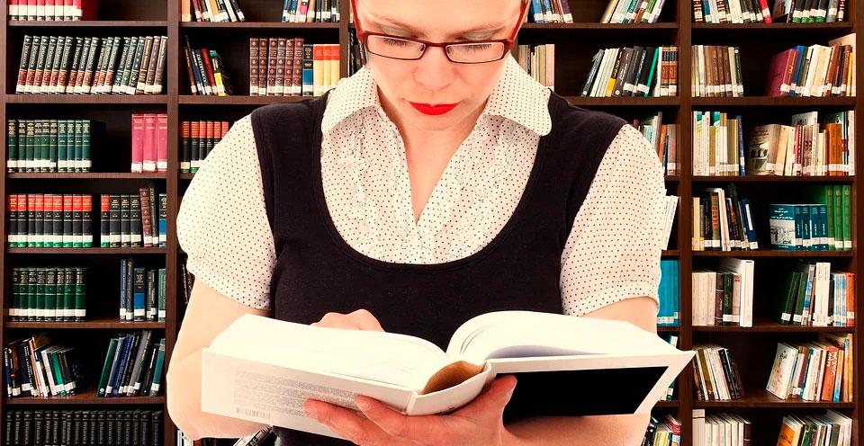 mulher lendo livro aberto nas mãos representando traduções certificadas